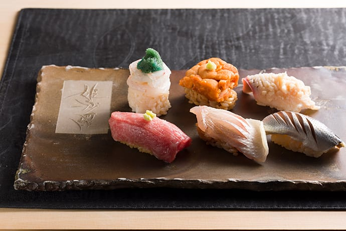 Each ingredient is finely crafted to create nigiri (hand-shaped sushi) with visual appeal and flavor.