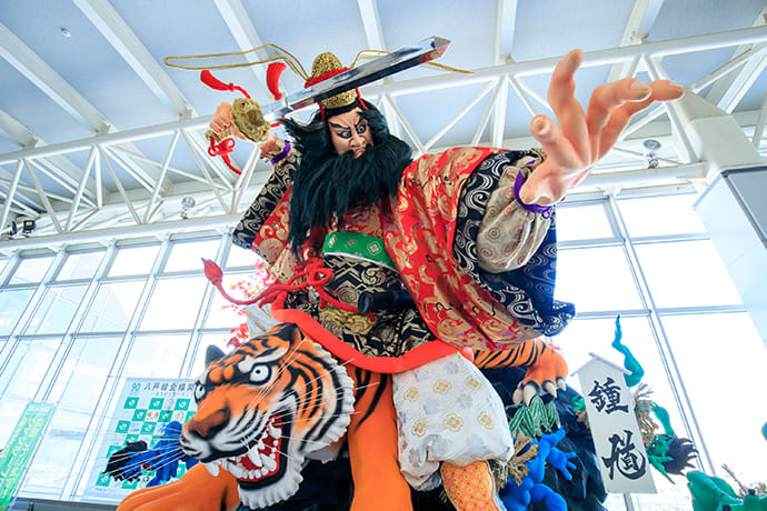 A dynamic figure from a Hachinohe Sansha Taisai festival float is on display at Hachinohe Station.
