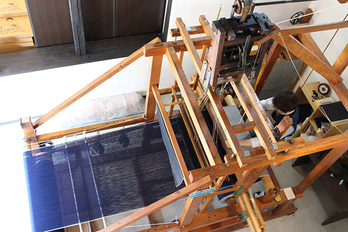 A Momotaro artisan at work on the customized denim weaving loom Photo credit: Japan Blue Co., Ltd.