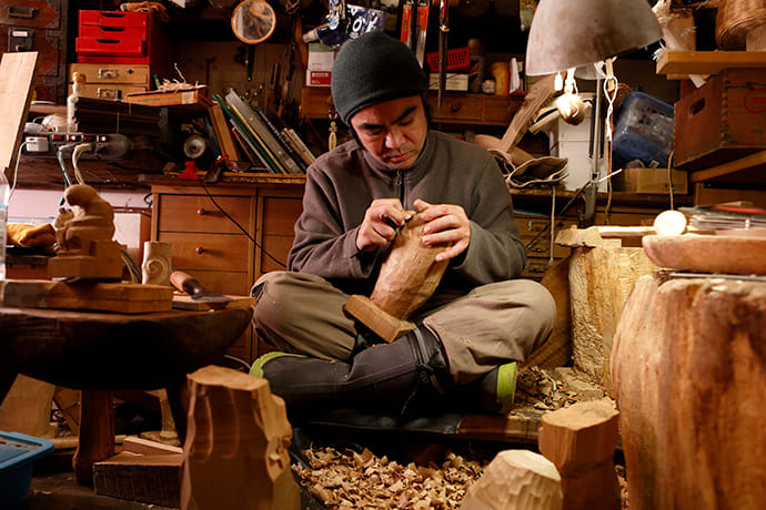 Kengo Takiguchi carves an artwork at Ichinge. He inherited the shop from his father, a renowned sculptor.