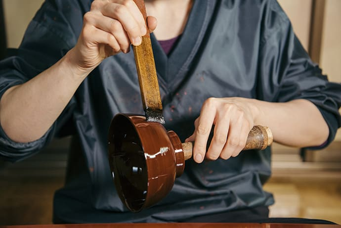 Applying the topcoat. Very few studios use precious Joboji lacquer for all coats.