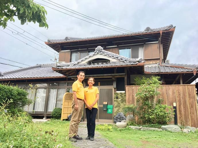 Mr. and Mrs. Toyoda stand in front of their farmhouse, Farmhouse NaNa.