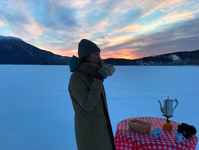 Drinking coffee in a dramatic frozen setting.