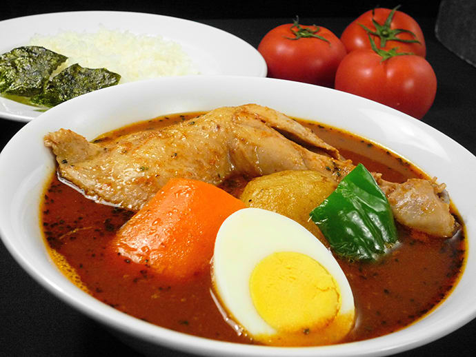 "The specialty, ""soup curry with chicken on the bone"" is served with a large chicken leg."