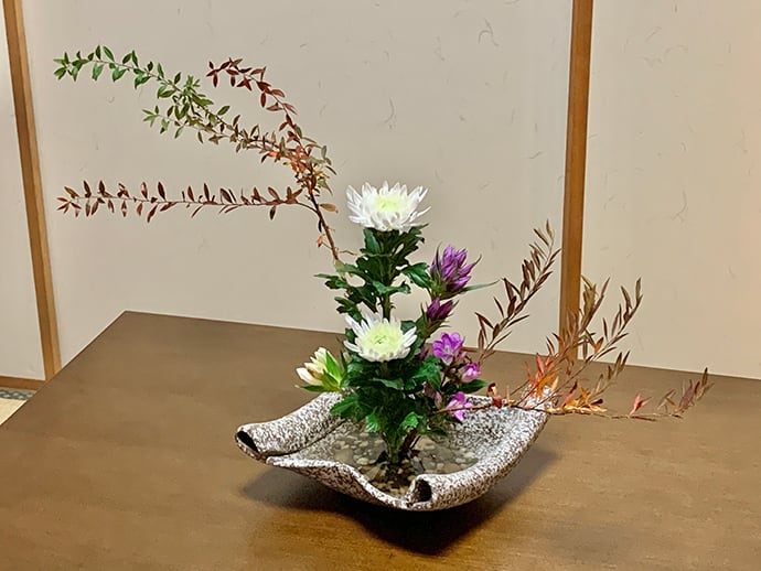 Autumn expressed in an ornate receptacle using chrysanthemum, Japanese gentian and Thunberg's meadowsweet.