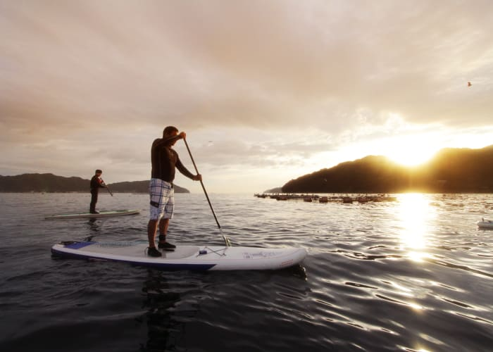 Stand-Up Paddleboard Along the Coastline of a Small Fishing Village