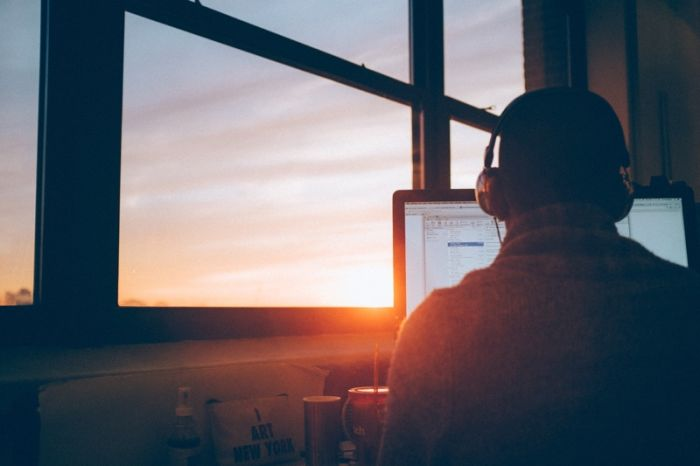 man working on a computer looking at sunset