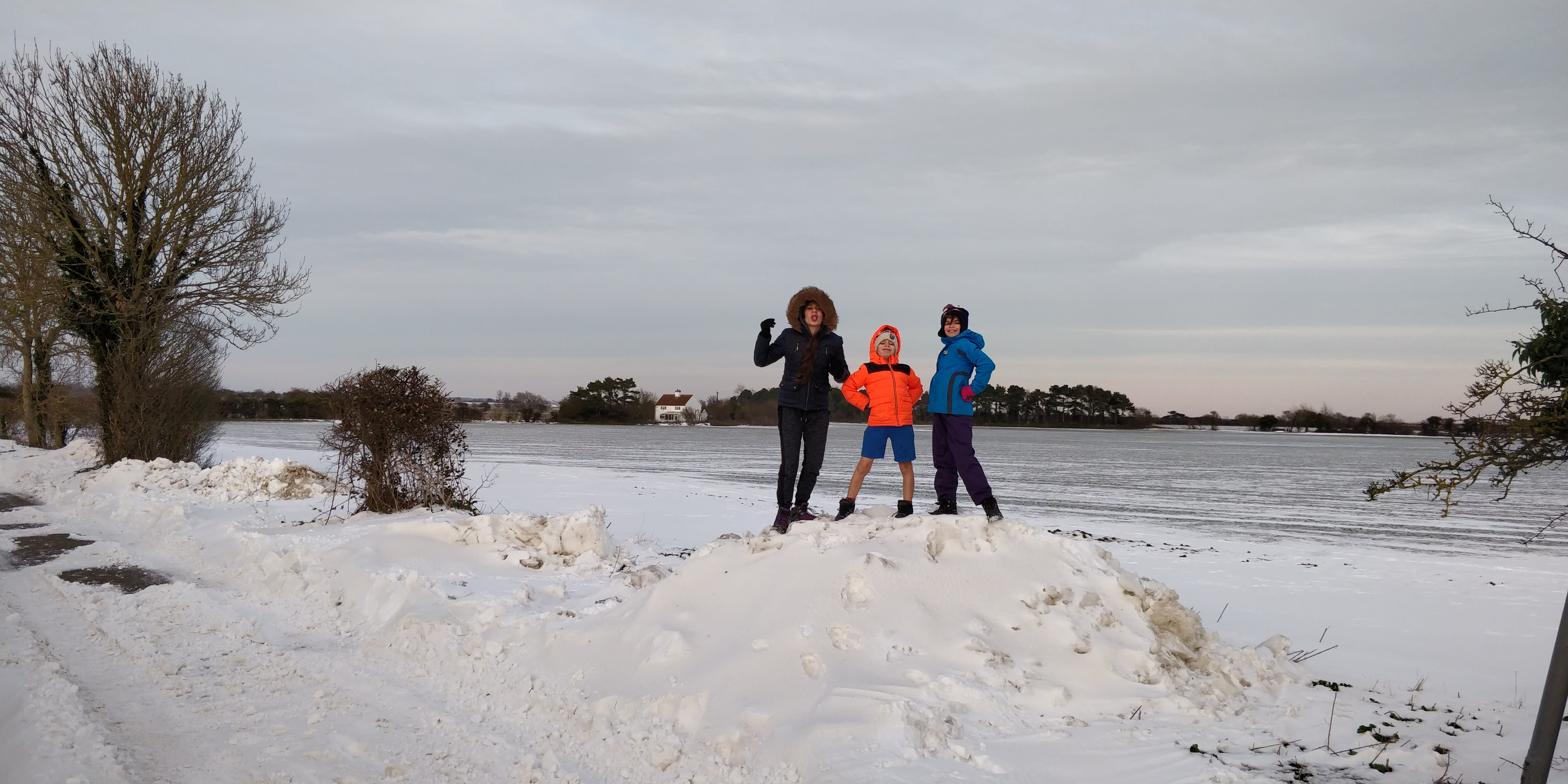 Our children ontop of a pile of snow