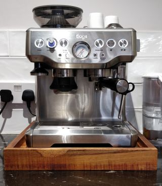 Photo of a silver coffee machine on a wooden tray