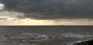 Photograph of the sea with dark clouds in the sky and ferry seen in the distance