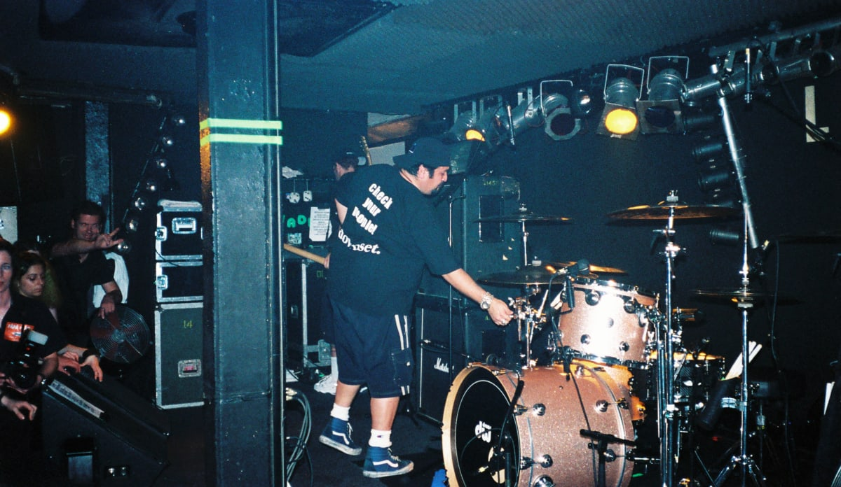 The Papa Roach drum tech adjusts the drums in preparation for the headliner