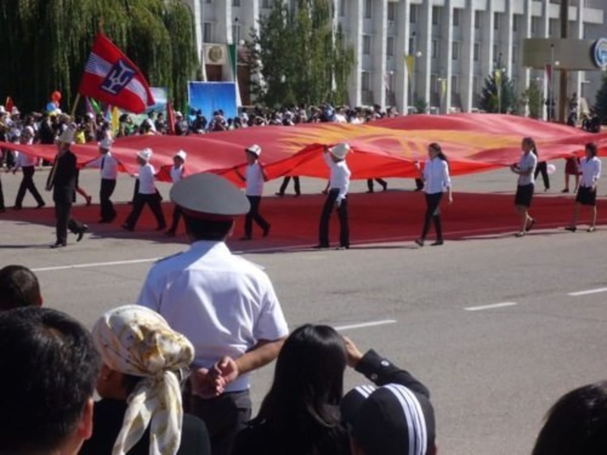 Youth carrying a giant flag of Kyrgyzstan