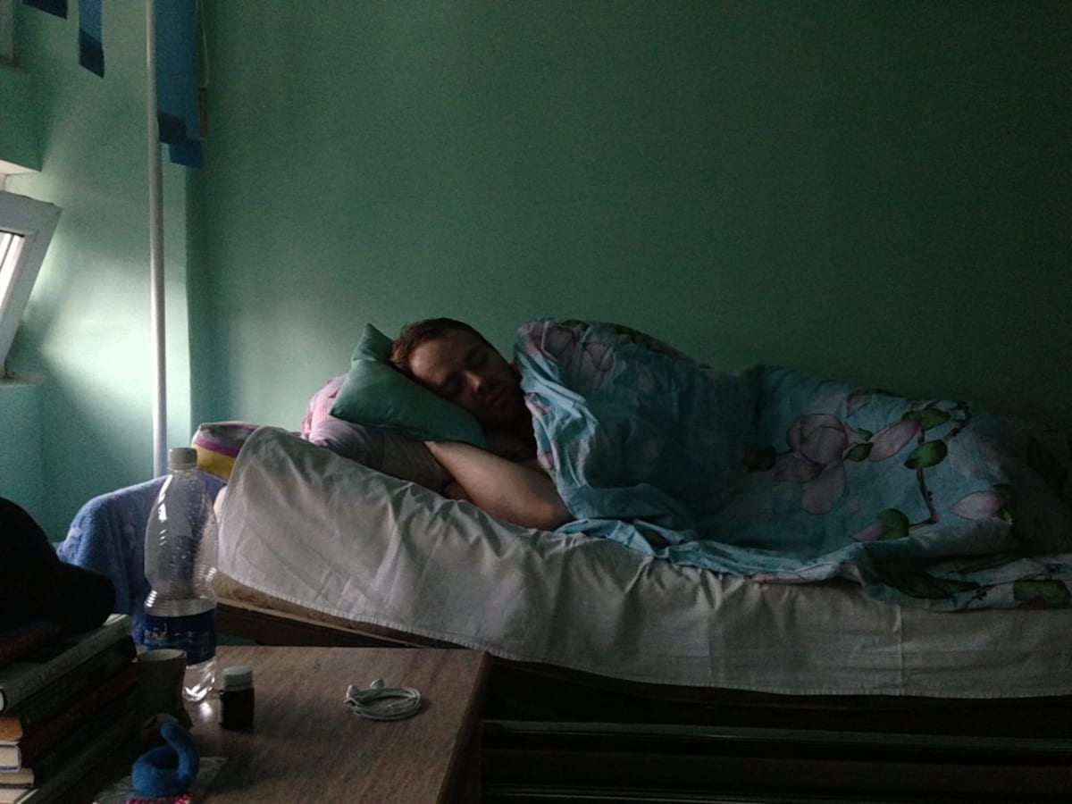 Judson recovering in a hospital bed after having an appendectomy in Bishkek.