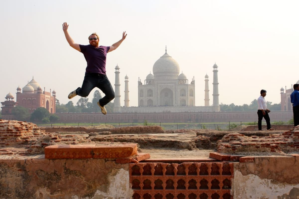India travel photo of man jumping in front of Taj Mahal