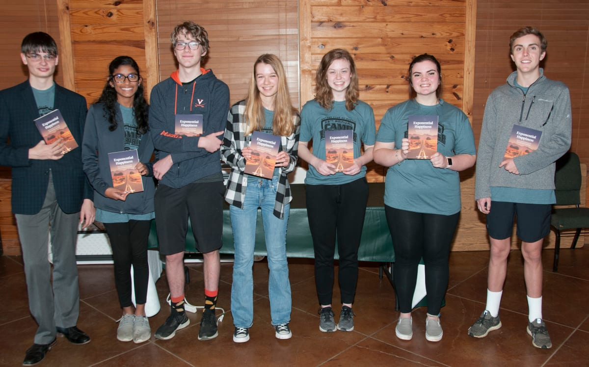 Students holding Judson's book, Exponential Happiness
