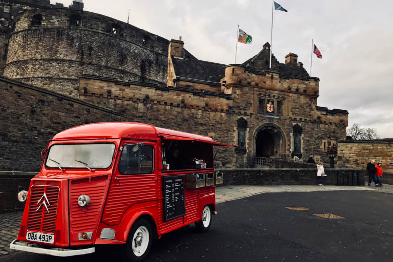 A red coffee truck stands in front of The Gatehouse at Edinburgh Castle