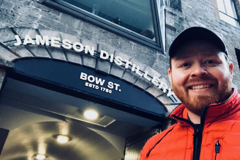 Judson stands in front of the entrance sign for the Jameson Distillery