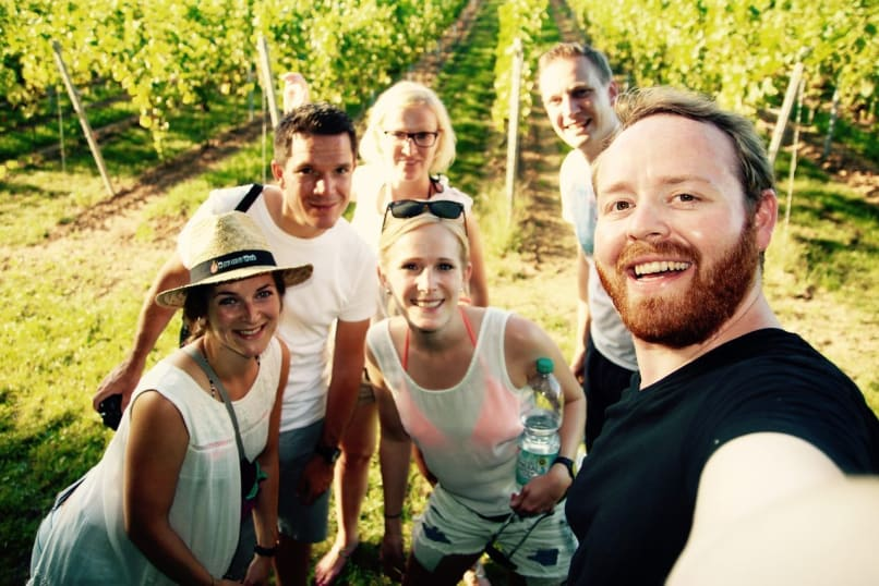 Friends in the German Wine Country walking through a vineyard.
