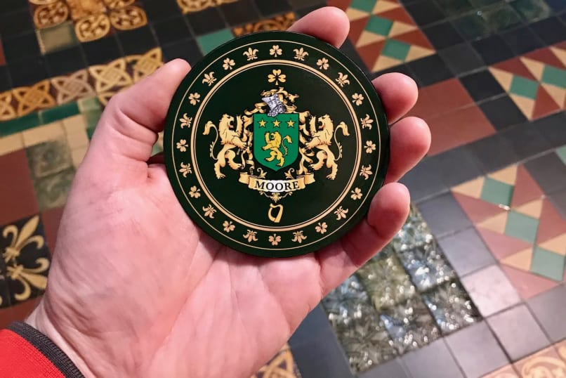 Judson holds the Irsh family crest for Moore. Two golden lions flank a green shield with three golden stars and a golden lion on it