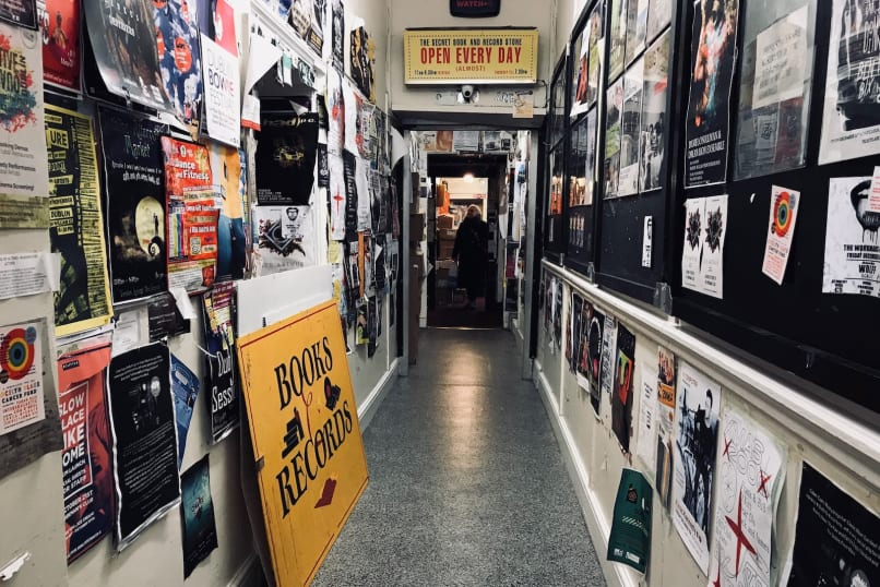 A long corridor with walls covered in posters and a bookshop at the end