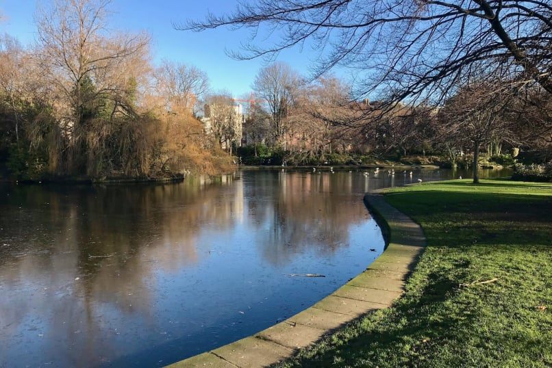 A winter view of a pond in St. Stephen's Green with blue skies