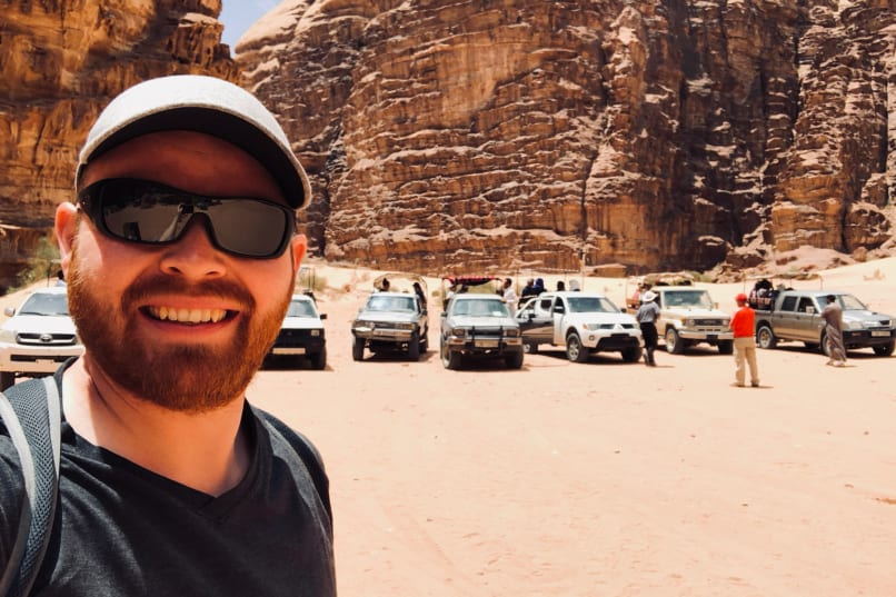 Judson poses with Wadi Rum tour jeeps in the Lawrence Memorial Bedouin Camp