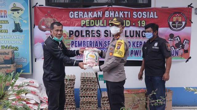 Kapolres Simalungun AKBP Heribertus Ompusunggu, SIK, MSI membagikan sembako secara simbolis kepada Ketua PWI Simalungun Efendi Damanik
