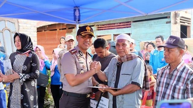 Kapolres Tanjung Balai AKBP Putu Yudha Prawira menyerahkan bantuan kepada salah satu warga korban kebakaran