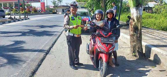 Personil Sat Lantas berikan bunga dan coklat kepada seorang pengendara sepedamotor yang tertib berlalulintas