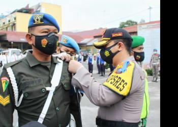 Kapolres Siantar AKBP Boy Sutan Binanga Siregar SIK menyematkan tanda pita kepada personil Denpom 1/1 Pematangsiantar perwakilan peserta Ops Keselamatan