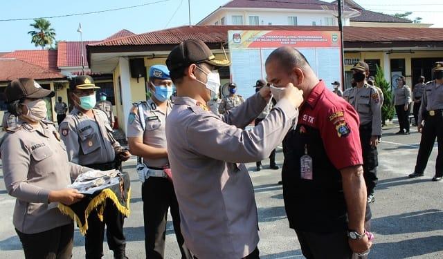 Kapolres Siantar AKBP Budi Pardamean Saragih, SIK, MH membagi maskser secara simbolis kepada salah satu Perwira