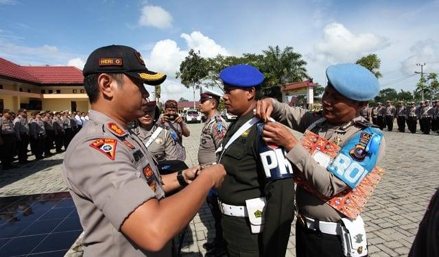 Kapolres Simalungun AKBP Heribertus Ompusunggu, SIK, MSI memasang tanda pita kepada salah satu personil peserta Ops Zebra Toba 2019