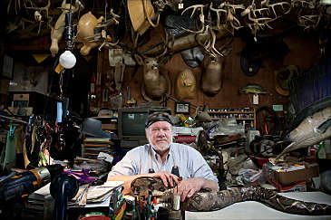 Posed portrait of a taxidermist in his workshop