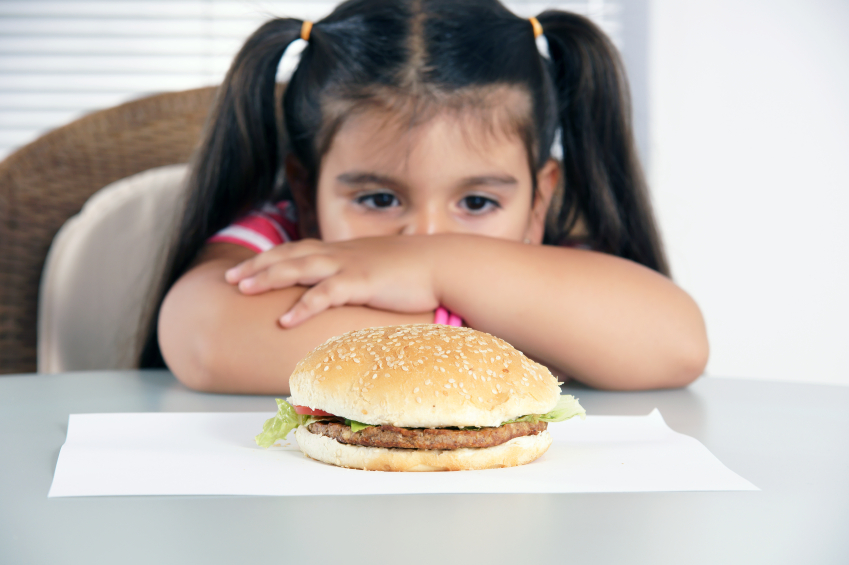 girl staring longingly at a hamburger