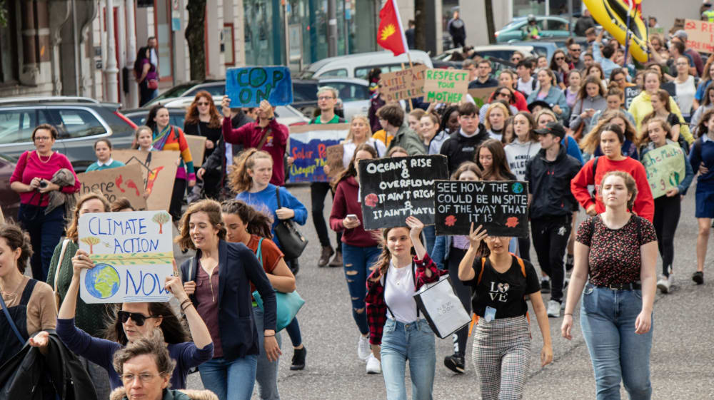 Students walking down a street protesting climate change