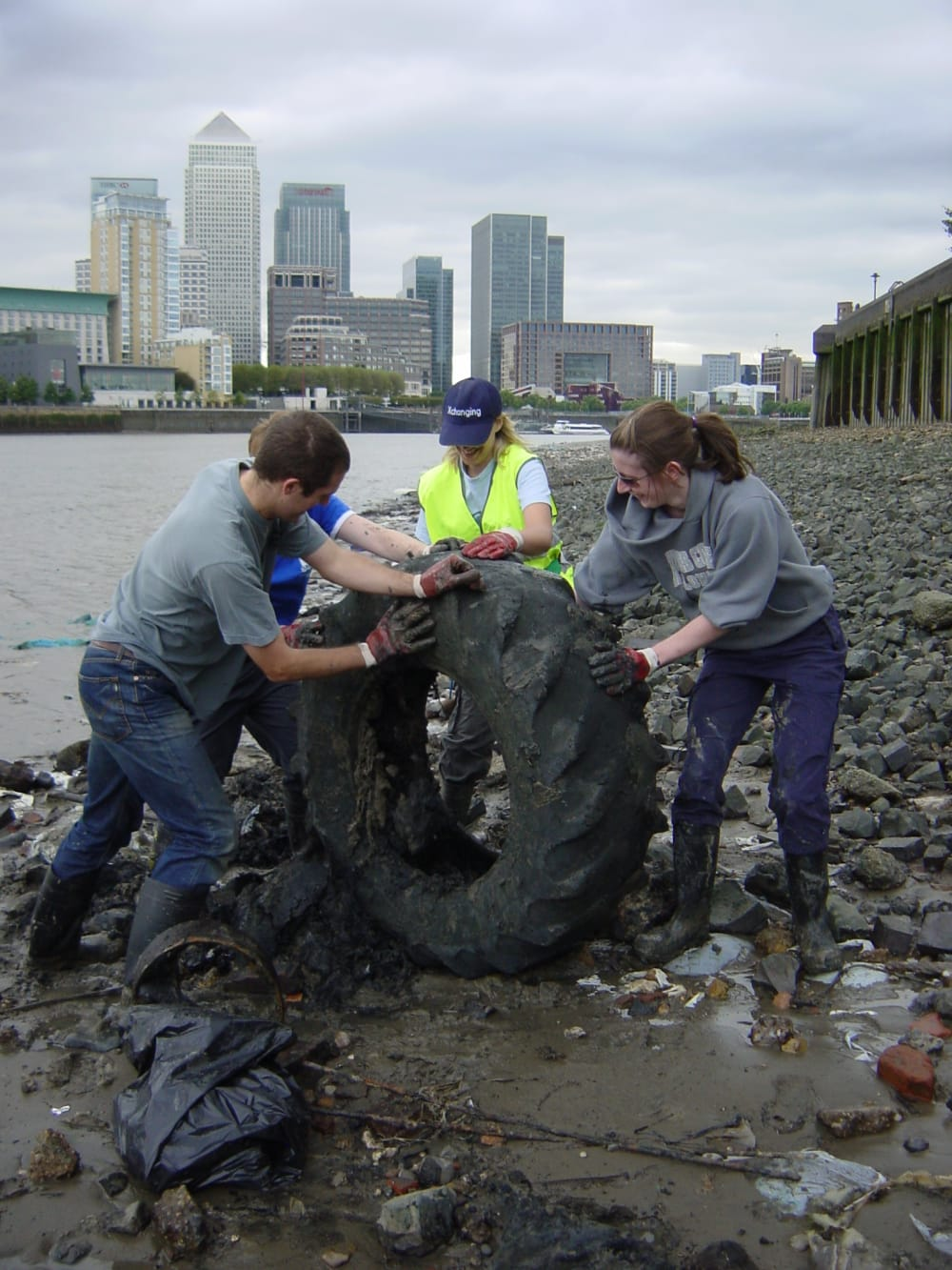 students on the Thames estuary helping lift a tyre