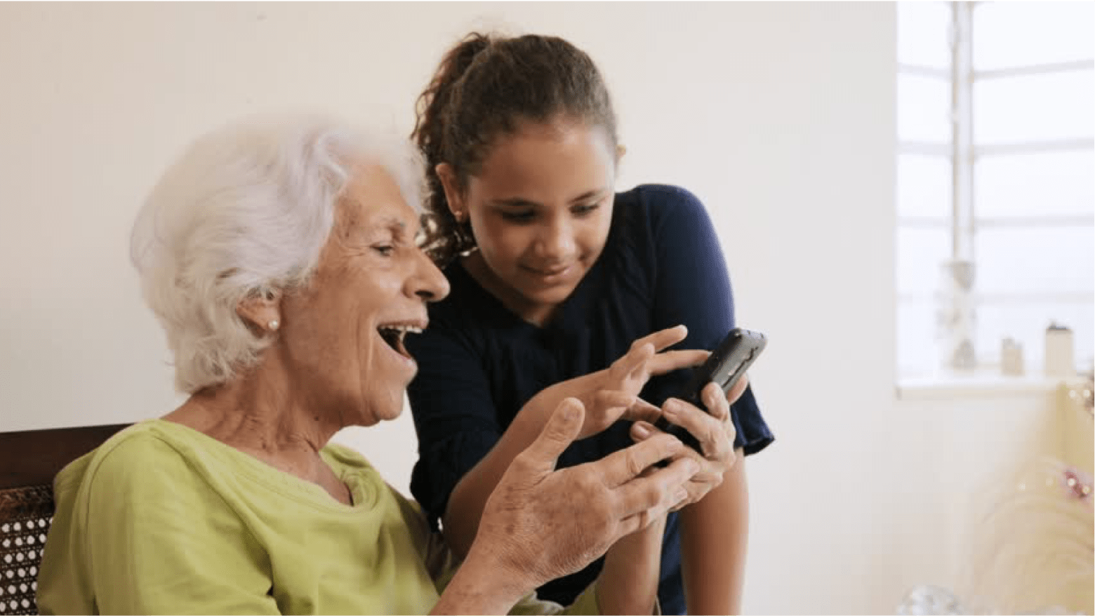 A kid helping an elderly with her phone