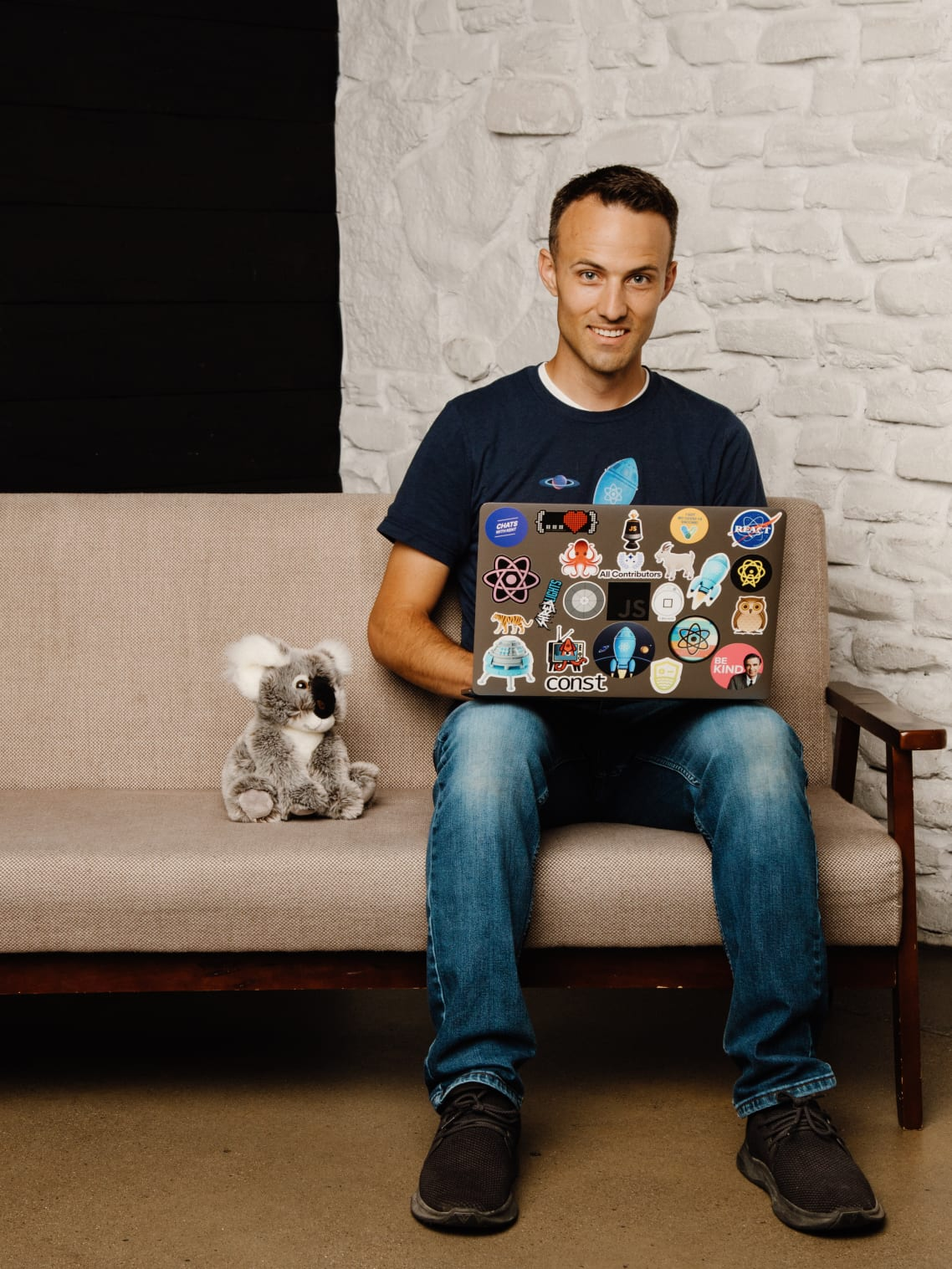 Kent sitting with his laptop on a bench next to Kody the Koala
