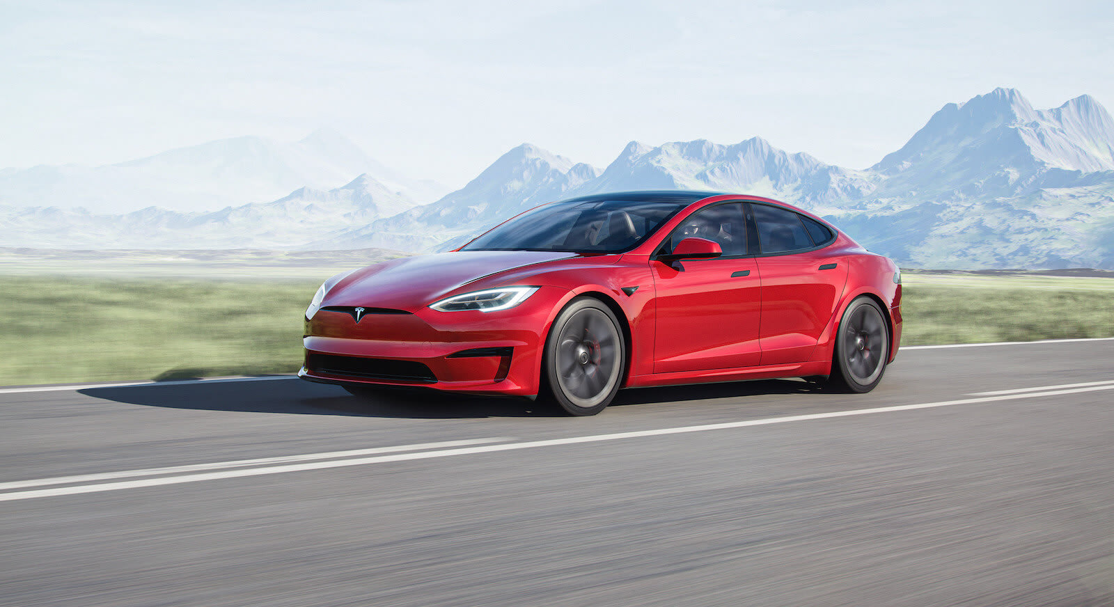 Tesla Model S driving fast with mountains in the background