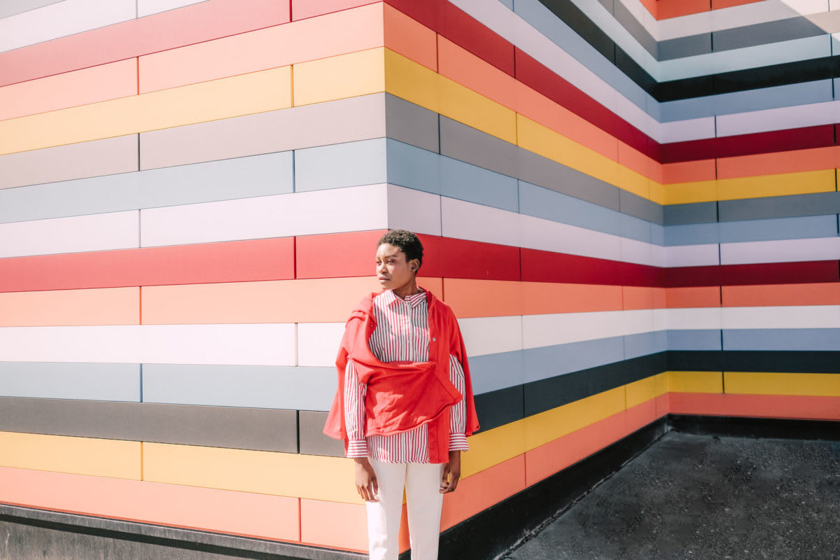 Girl poses against vibrant striped building