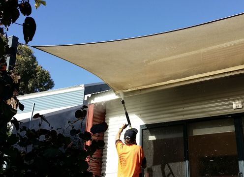 Cleaning the underside of a canopy with a water jet.
