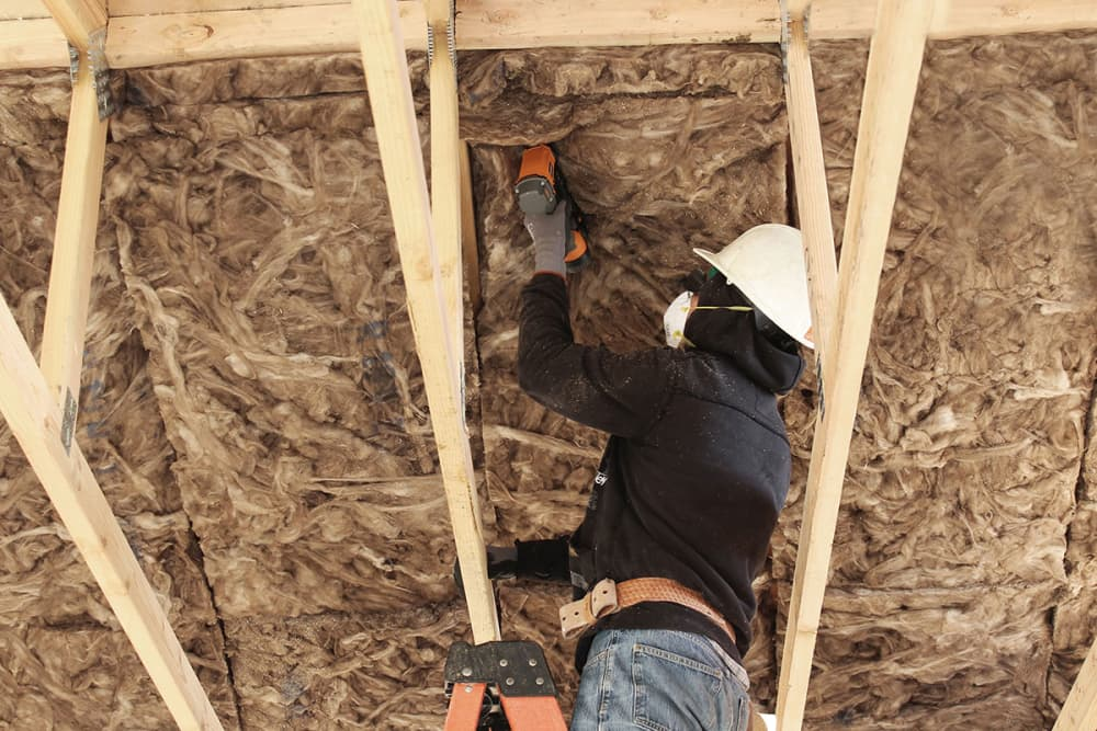Installing integrated roof deck batt insulation for roof decks and mid-floors to meet title 24 requirements.