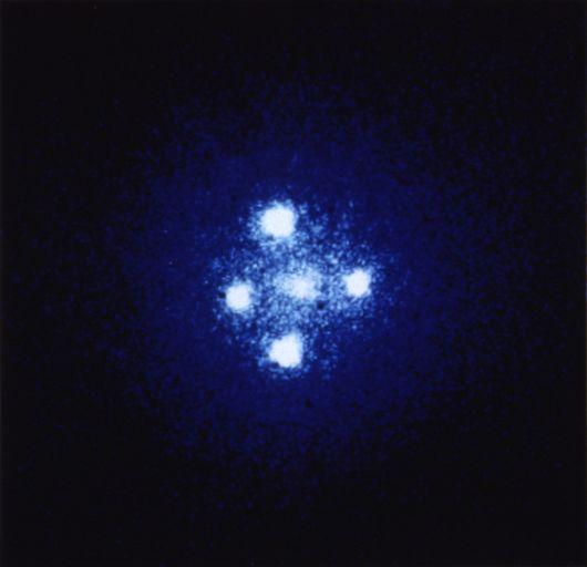 Эффект гравитационного линзирования, известный как крест Эйнштейна. Четыре изображения одного и того же квазара обрамляют близкую к нам галактику.