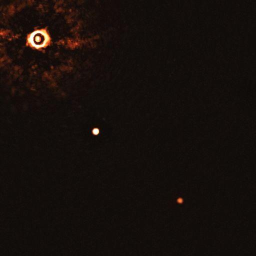 Снимок, полученный приёмником SPHERE на VLT. Свет от звезды блокирован при помощи коронографа. Светлые и тёмные кольца в поле вокруг звезды – оптический артефакт. Планеты видны как две ярких точки в центре и в нижней правой части кадра.
