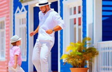 glücklicher Vater und Sohn genießen das Leben, tanzen auf der karibischen Dorfstraße