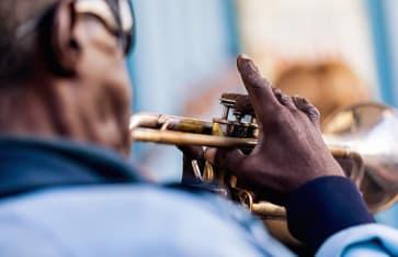Ein alter schwarzer Mann mit blauer Jacke, der Trompete spielt. Vinales in Kuba.