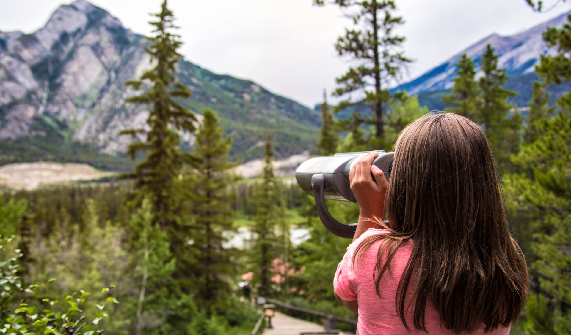 Ein Mädchen schaut durch die Ferngläser im kanadischen Nationalpark Banff