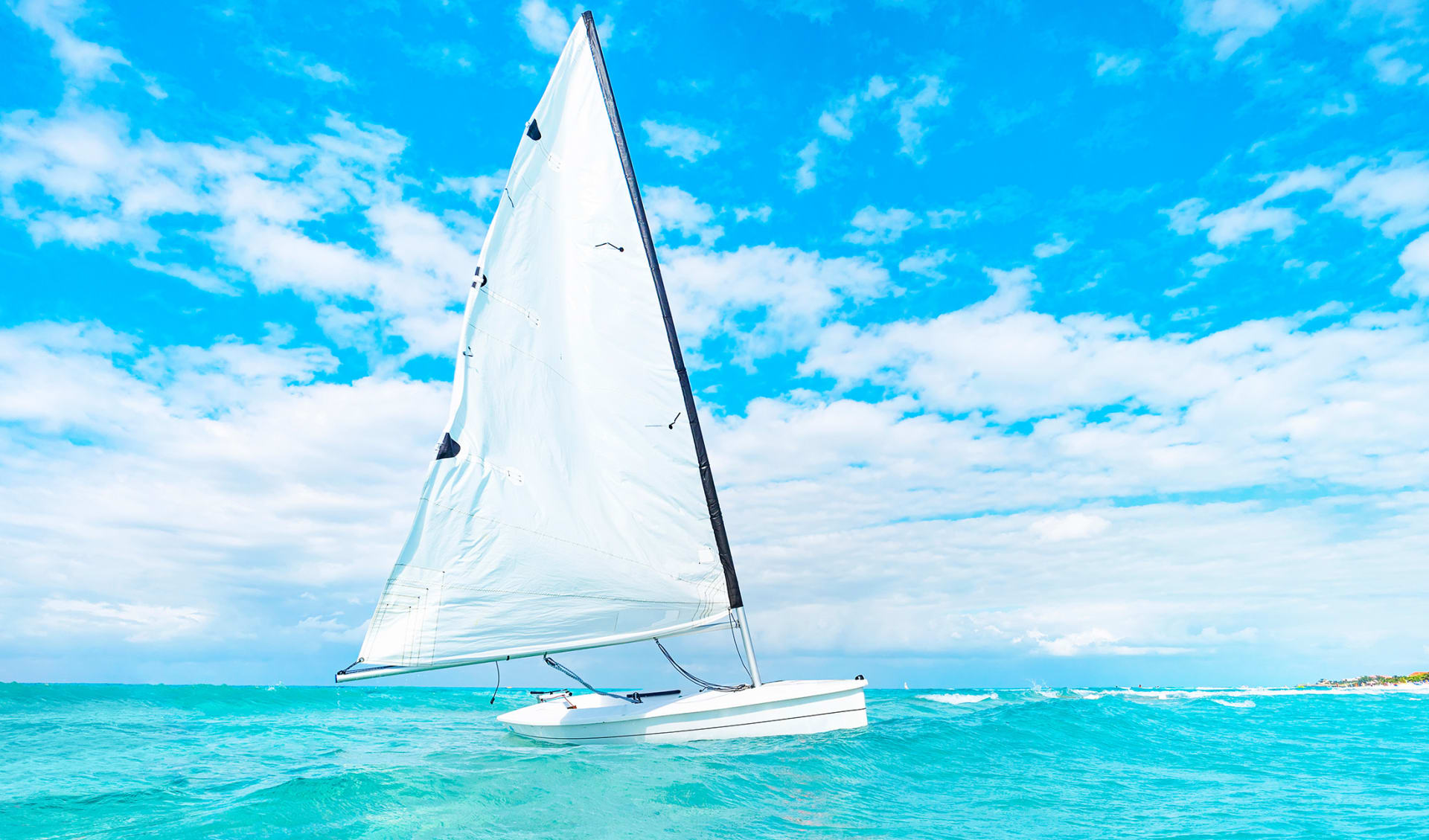 view of catamaran sailing in ocean open water. A catamaran with a white sail drifts through the turquoise waters of the Caribbean sea without people. Beautiful scenery.
