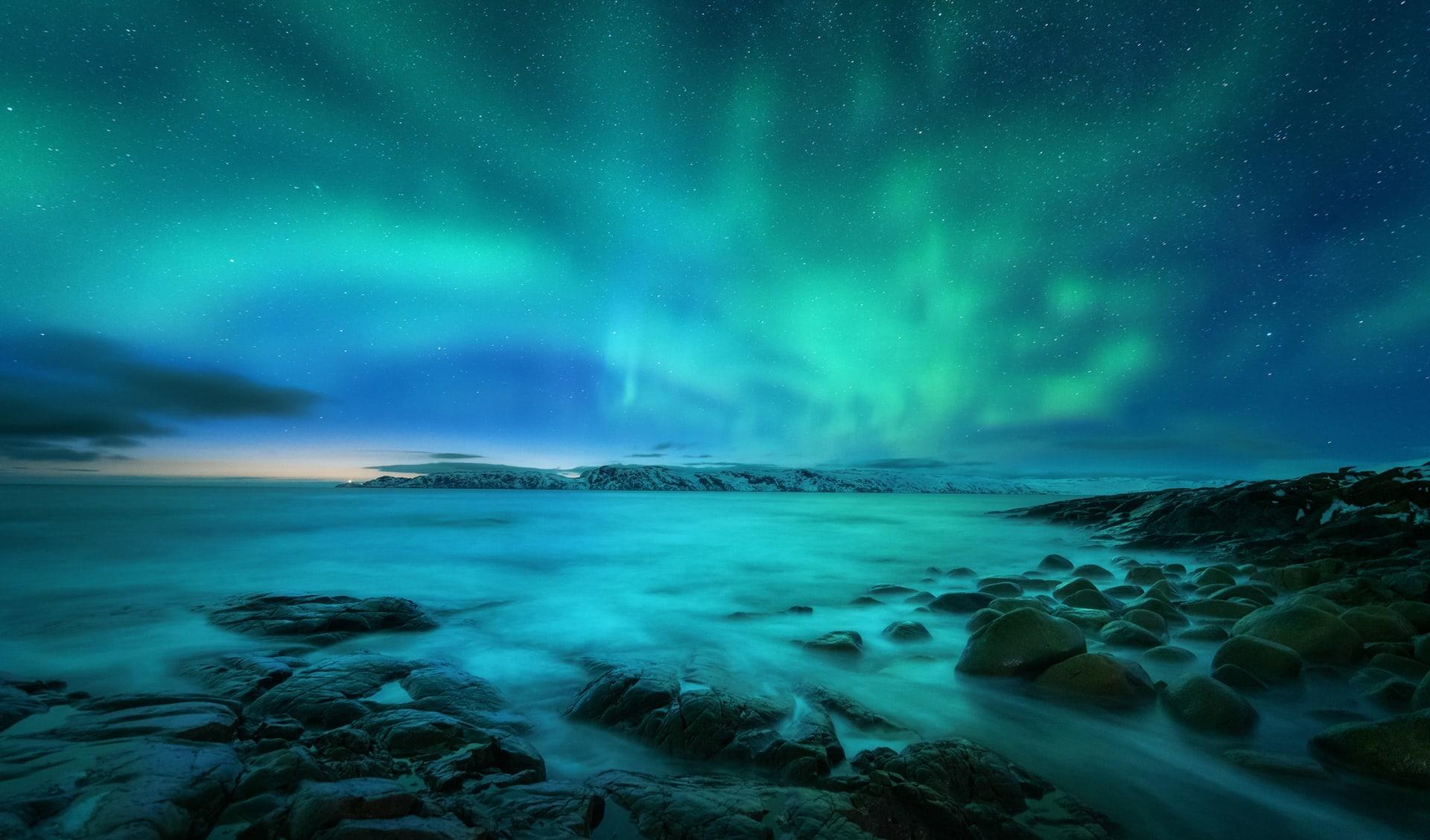 Aurora borealis über Felsstrand und Ozean, Island