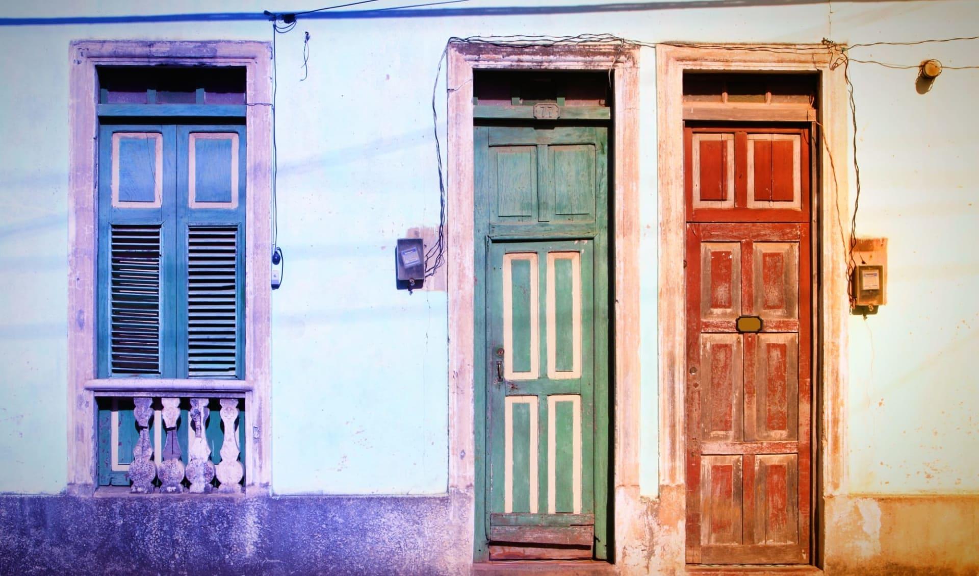Portrait einer Insel ab Havanna: Stadt Baracoa - farbige Häuser in Baracoa - c